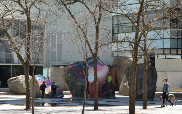 Devonian Square in Toronto, large open area with wading pool (empty at the moment) and large boulders, small trees growing around the edge of the pool, two people walking through the pool area, a woman walking her dog on the sidewalk beside, rocks covered with artwork