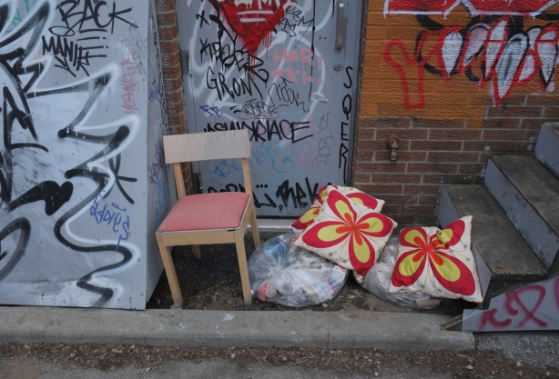 door in an alley with a chair in front of it as well as bags of garbage and two bright red and yellow cushions