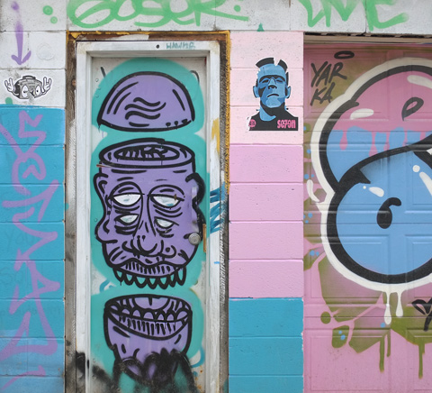 door in an alley with street art in purple and teal, two paste ups, on on either side of the door