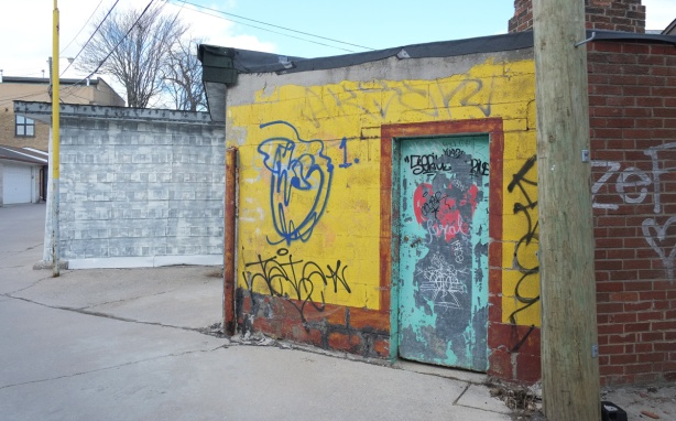 yellow building (shed? garage?) in an alley painteed white with light teal door with graffiti on it