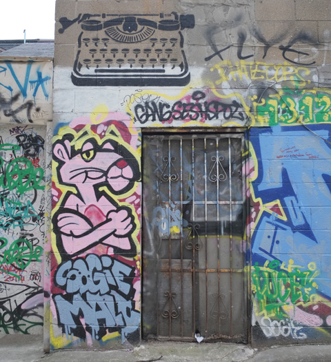 painting of the pink panther cartoon character standing beside of real door covered with a metal grille