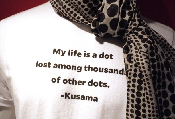 on a mannequin, a white t-shirt and a polka dot scarf. The t-shirt has writing that says, My life is a dot lost among thousands of other dots, Kusama