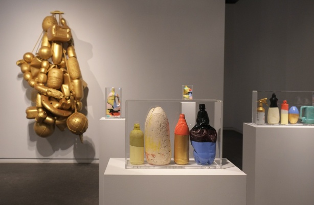 plastic containers and other items found washed up on the shore of British Columbia, cleaned up and painted and put in sealed clear plastic boxes, art gallery exhibit, artis is Douglas Coupland, with large structure behind made of gold painted containers and other items
