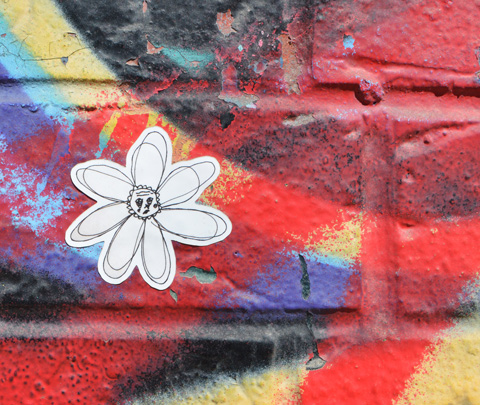 a small black and white daisy drawing on a sticker on a wall that is covered with bright paint