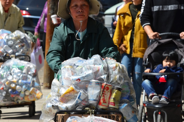 An older Chinese woman is pushing a cart with a large clear plastic bag full of empty aluminium cans, a Chinese man with a similar cart is behind her, other people out walking  on the sidewalk