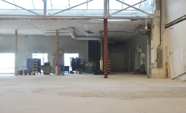 looking through a window into a large open space, some construction equipment is against the far wall, large door open across the room
