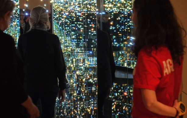 a woman is entering Kusama's room with many lights and mirrors