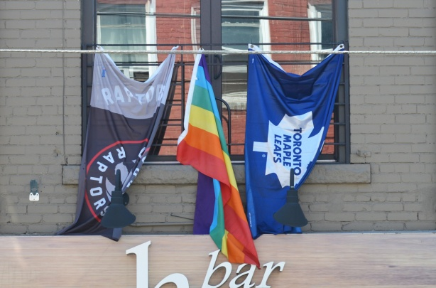 three flags hanging outside a window, a Raptos flag (Toronto basketball) and a Maple Leafs flag (Toronto hockey) as well as a rainbow pride flag