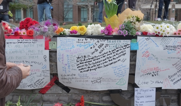 white bristol board taped to a stone wall, condolences and other heartfelt messages written on them, flowers laid across the top of the wall