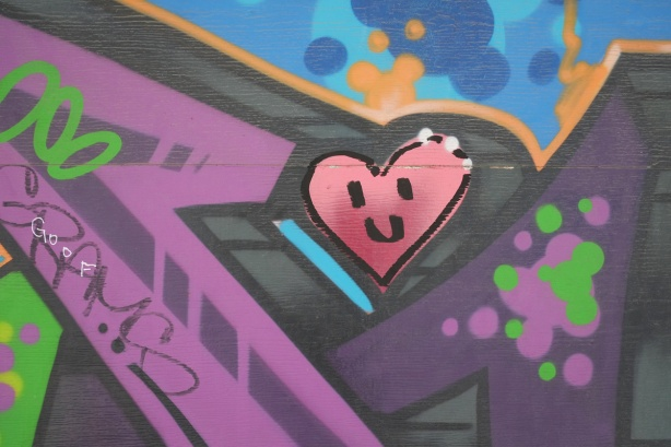 pink smiley heart on a wall with lots of other colours, street art