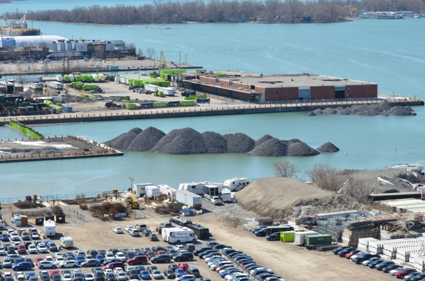 view from higher, over Keating channel, Essroc quay and towards Centre Island, Port lands in Toronto, mounds of gravel in the water, parked cars, boats in the water, light industrical development, trees,