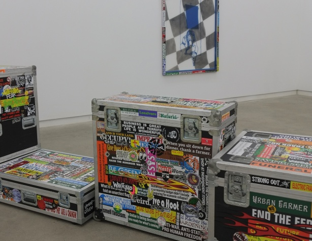 sticker covered metal cases on the floor of an art gallery with a picture on the wall behind, the work of Niall McClelland at the Clint Roenisch gallery