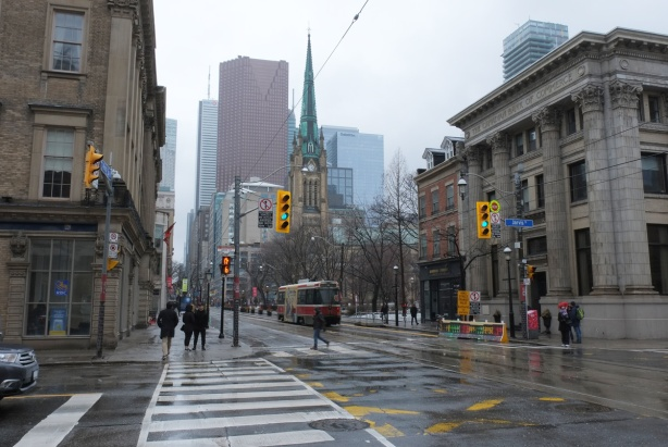 looking west on King street from Jarvis, St. James Cathedral and park on the right, downtown towers and office buildings in the distance, rainy day, TTC streetcar,