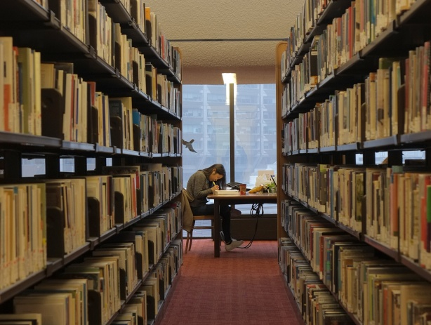 looking down an aisle between two stacks of books (book shelves), a woman is sitting at a table studying and writing, there is a window behind her