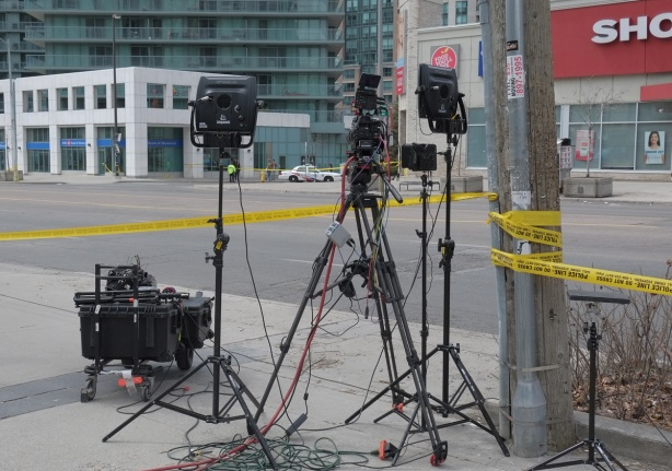 camera, and lights on tripods abeside Yonge Street, yellow police tape blocking the street, police car in the background, no traffic