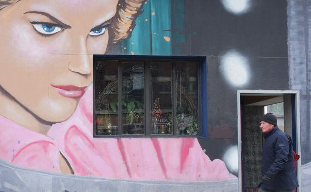 Cameron House mural on Queen Street West, woman in pink blouse is looking beyond the window to a man walking past.
