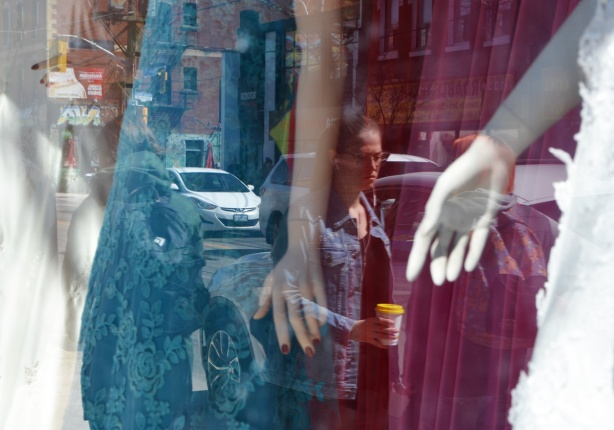 a window with mannequins in long dresses, teal and magenta fabric, reflections of woman passing by with a coffee cup in her hand