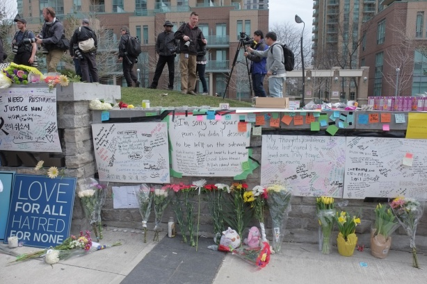 white bristol board taped to a stone wall, condolences and other heartfelt messages written on them, flowers laid across the top of the memorial wall