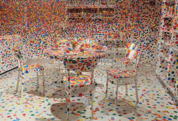 a room all white, including white furniture is covered with dots in many colours, stickers that different people have added to the room. Part of exhibit at AGO of work by Yayoi Kusama