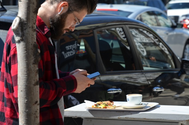 a man outside, standing on sidewalk, with a plate of food and a cup of coffee,, with his phone in his hands