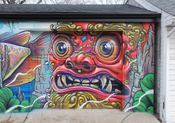 part of a mural on a garage door by Bruno Smoky, a large red face of a man.