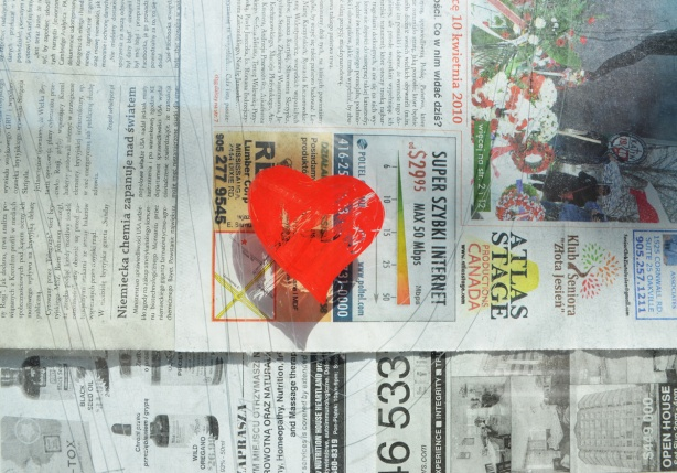 a small red heart is painted on the window of a store that is now empty and newspaper covers the inside of the window.
