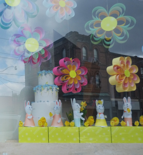 looking into a store window, that is decorated with little bunnies in Easter clothing, with little yellow chicks and paper flowers