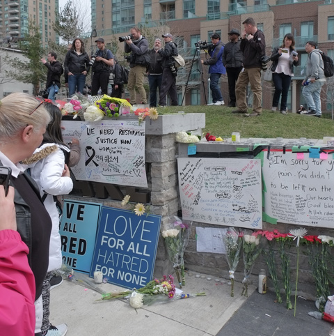 a woman is writing condolences messages on bristol board that has been taped to a stone wall