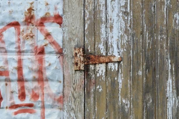 rusty hinge on wood door with paint peeling