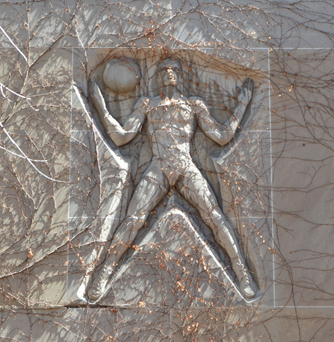 on a wall, covered with ivy plant (early spring so no leaves), relief sculpture of a man with legs spread apart, with a ball on his shoulder, arms bent upwards at elbow