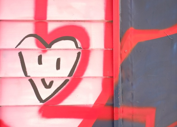 smiley heart on pink wall with red spray paint lines around