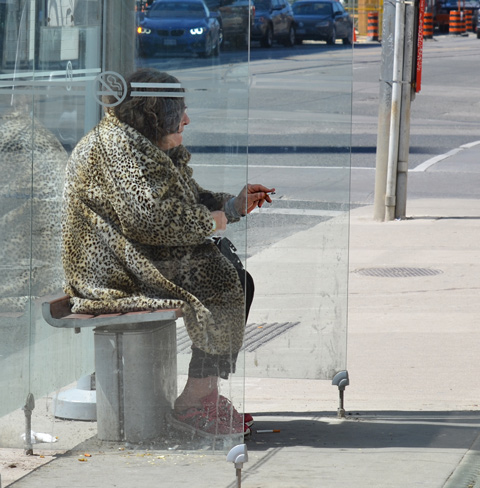 an older woman in pink running shoes and leopard print fuzzy jacket is sitting in a bus shelter, smoking a cigarette,