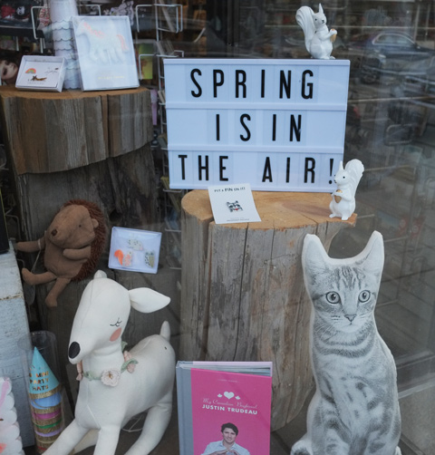 sign in a store window that says spring is in the air. also some stuffed animals