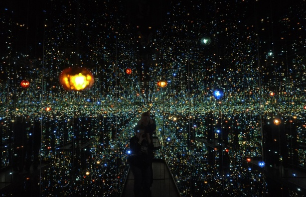 dark room with lights that look like planets and stars, mirrors on walls and ceiling.