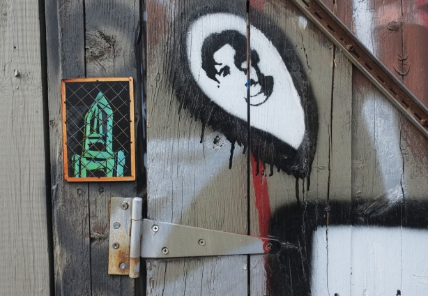 picture of a green stikman in a little frame, on a wood gate, by a black and white stencil of a man's head