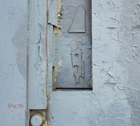 a broken stikman painted greyish blue on a greyish blue door where the paint is peeling and the wood is fraying