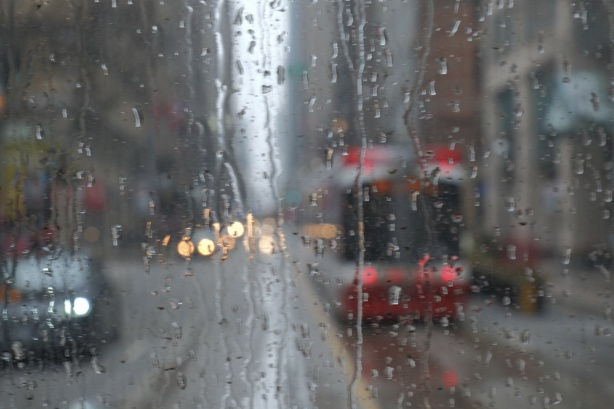 looking out the back window of a streetcar, rainy day, raindrops on the glass, another streetcar is passing by