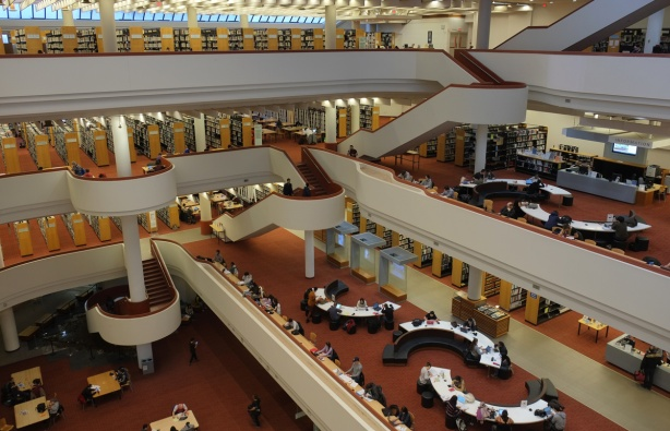interior of the Toronto Reference Library from the fifth floor, semi circular tables, reddish carpet, open concept architecture, rows of books,