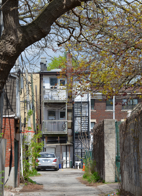 looking down an alley to the back of a triplex (three storeys high) with fire escape stairs and balconies with railings