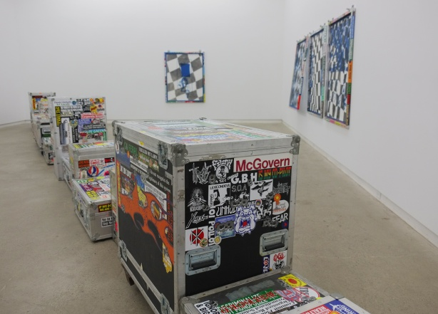 room in an art gallery, a line of trunks runs diagonally across the room, they are covered with bumper stickers.