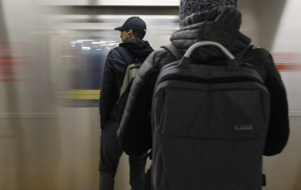 two people with their back to the camera wait on the subway platform as a train arrives