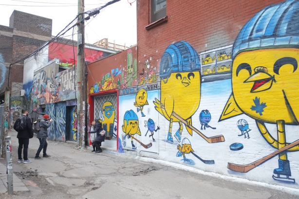 two women are having their picture taken in front of Uber5000's mural about Toronto in the winter, little yellow birdies playing hockey.