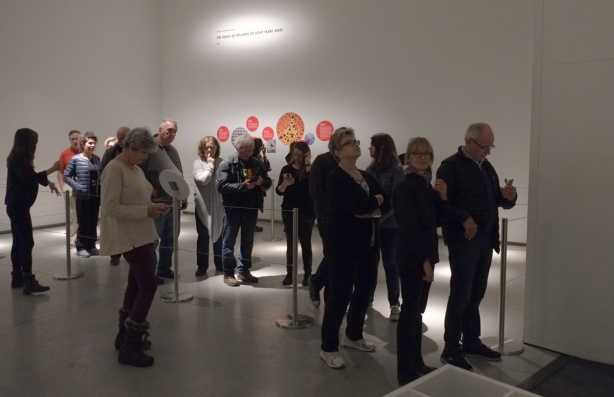 people lining up inside an art gallery