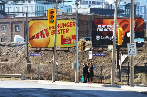 two people standing on a sidewalk as they try to figure out how to cross the street, two large billboards behind them, train tracks (elevated) behind that.