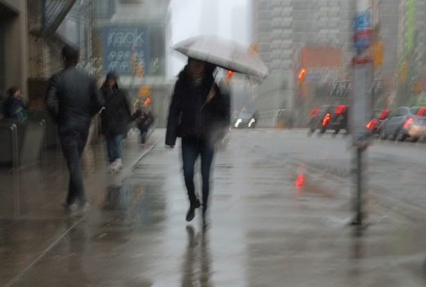 hazy, blurry picture of a person walking with an umbrella up Yonge street with other people, cars, wet sidewalk,