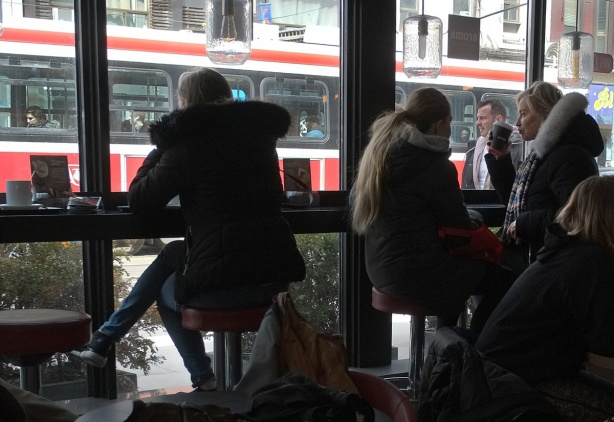 interior of a coffee shop, people sitting at tables, people sitting on the bar by the window, a TTC streetcar is outside, passing by