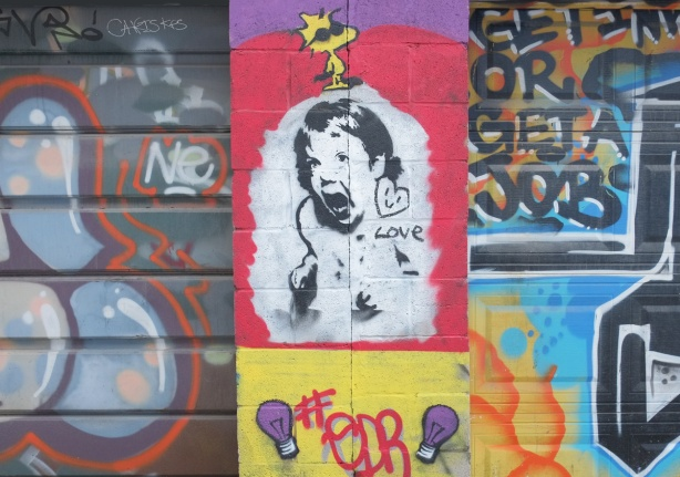 street art on garages, a small yellow Woodstock cartoon character with black sunglasses, on top of a black drawing on white of a girl screaming, a little smiley heart and the word love is beside her ear.