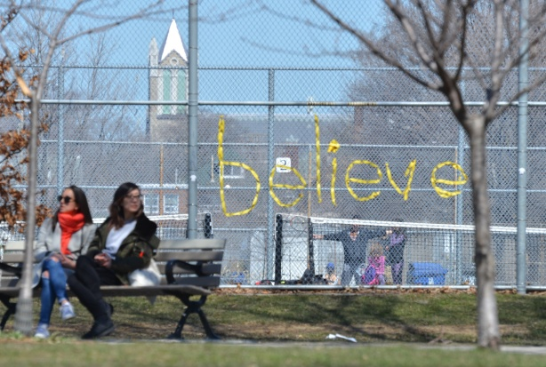 the word believe is written in yellow ribbon that has been woven into a chainlink fence around a tennis court, two women on a bench to the side of it, park,