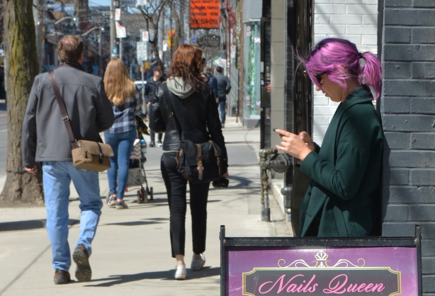 a woman with magenta hair is standing on the sidewalk, back against a wall.
