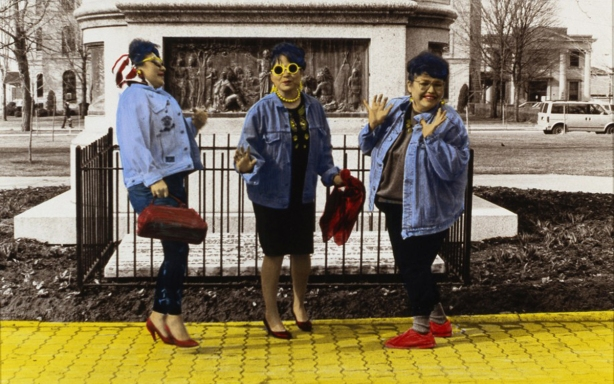 a colourized black and white photo of three women hamming it up for the camera. All wearing red shoes and walking on a yellow sidewalk, beside a metal fence. by Shelley Niro